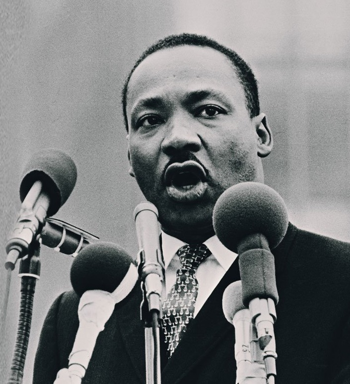 photograph of MLK speaking into microphones