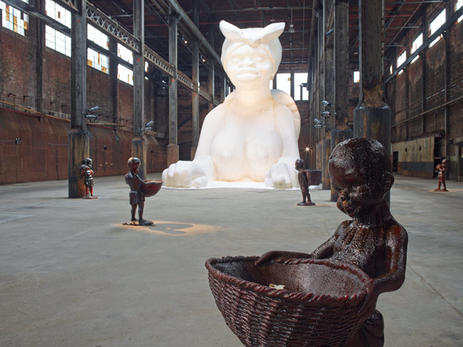 photograph of part of Kara Walker's A Subtlety, depicting female sugar sphinx and molasses children