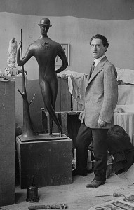 Elie Nadelman standing next to his sculpture Man in the Open Air