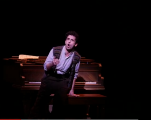 Brandon Uranowitz as Adam, the show's framer and narrator. He and his piano are often shown tiny on an otherwise bare stage.