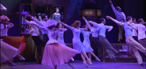 Screen shot from official Broadway video. Ensemble dancing at the Galeries Lafayette.