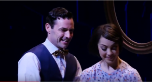 Look at that dorky bow-tie. (Max von Essen and Leanne Cope as Henri and Lise; screen shot from official video.)